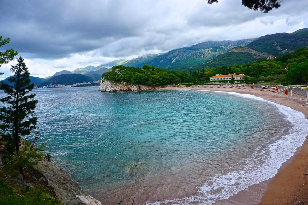 View of sandy beach, green mountains, gloomy skies, and lush forests in Sveti Stefan, near Budva, Montenegro.