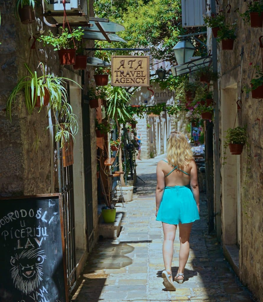 Woman in blue romper walking through the Old Town of Budva, Montenegro, one of the most popular Dubrovnik day trips.