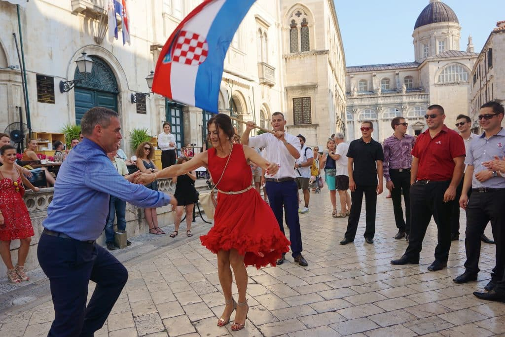Man and woman dancing next to another man waving a Croatian flag while a crowd looks in Dubrovnik, Croatia. The Stradun is an ideal place for people watching.