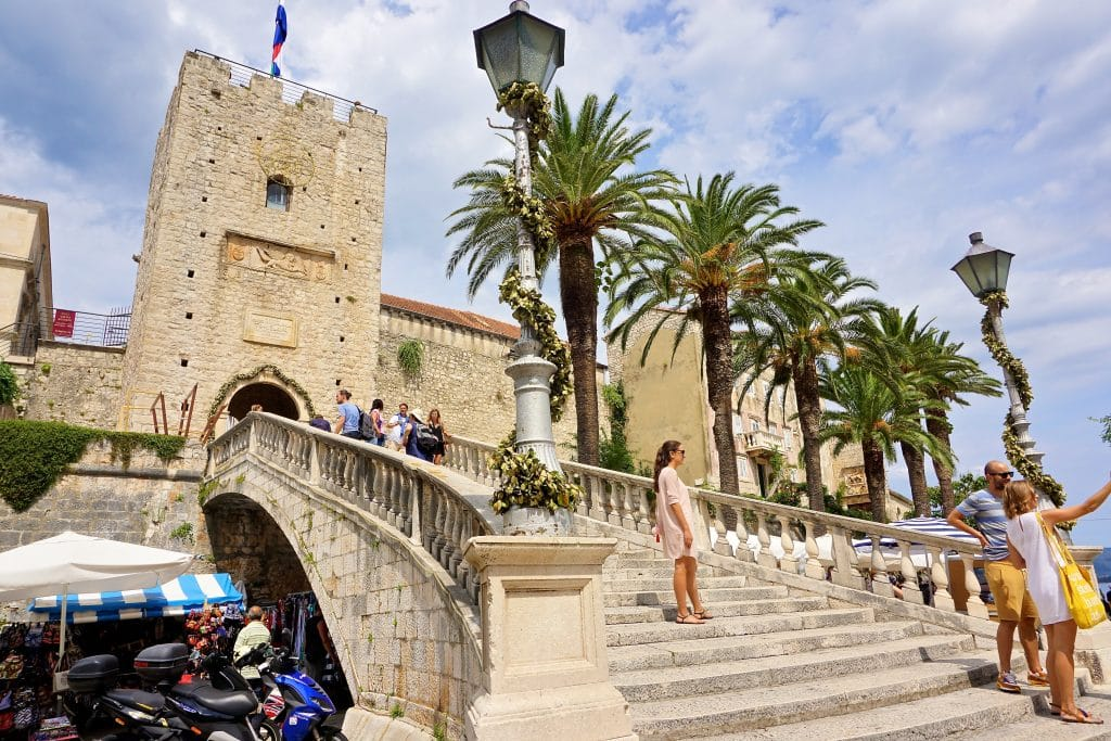 Ston archway bridge with palm trees into the entrance of Korcula Island's Old Town. Korcula is an ideal day trip from Dubrovnik.