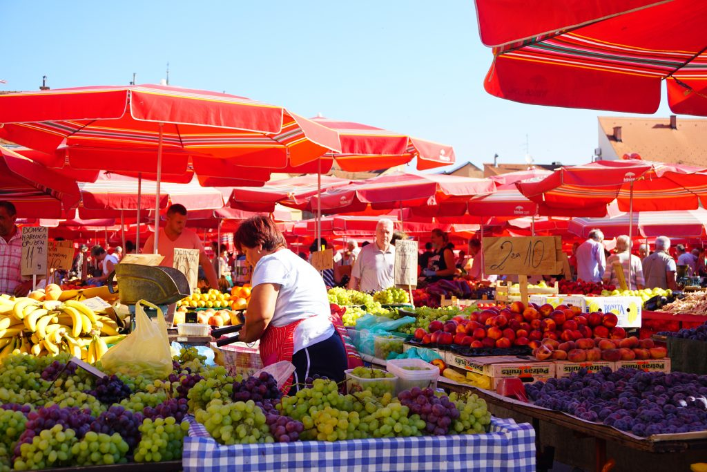 Dolac marketing in Zagreb with woman picking fresh produce.