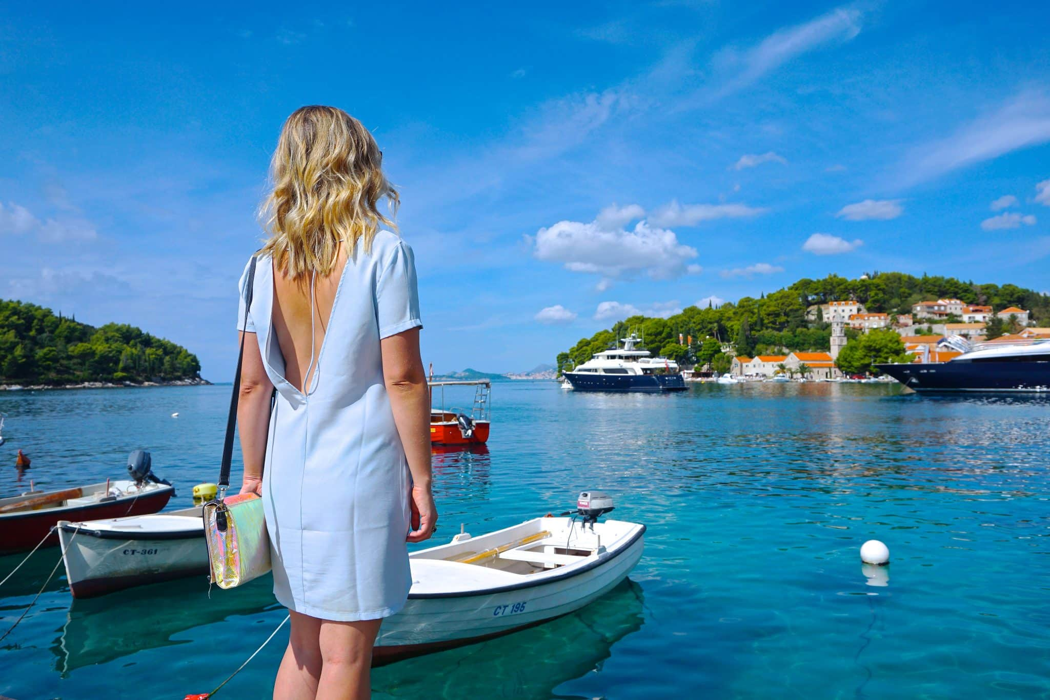 Woman standing on the dock in Cavtat, Croatia, surrounding by the Adriatic sea, small fishing boats, and green forests. Cavtat is an ideal day trip from Dubrovnik.