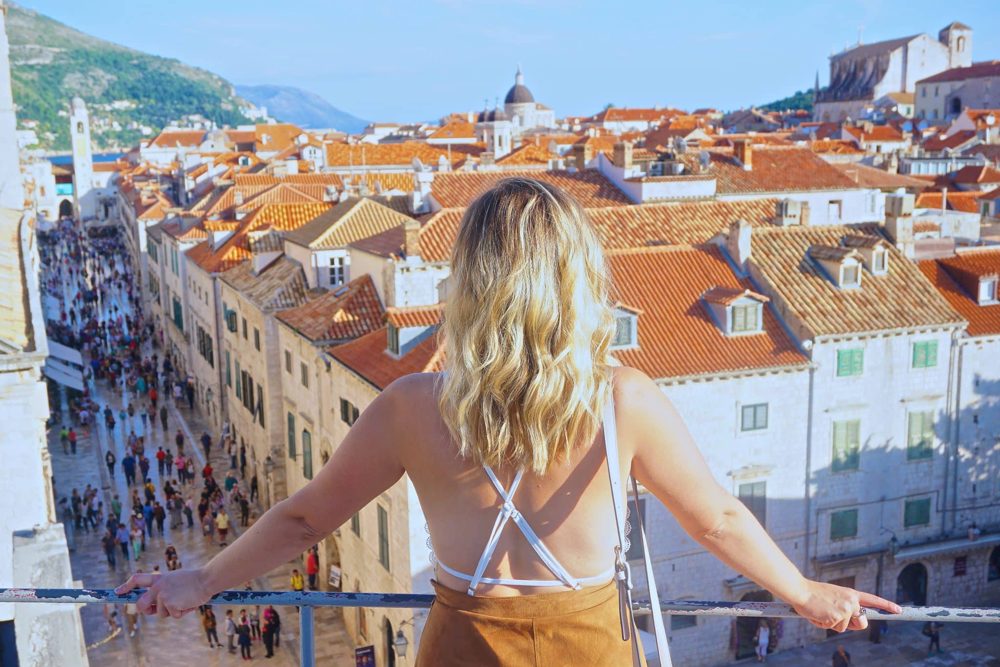 """Blonde woman in tan skirt looking over Dubrovnik's Old Town with orange roofs and the """"Stradun"""" street. This is a must see to add to any Dubrovnik travel guide."""