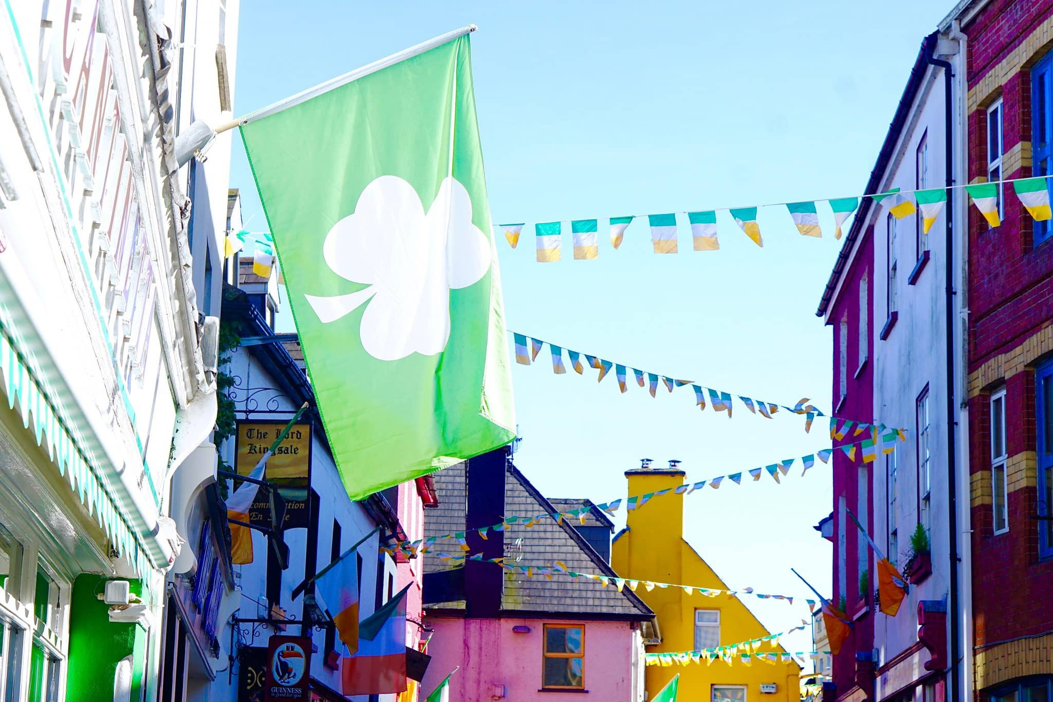 Colorful painted buildings in Kinsale Ireland, with Irish flags and a lucky clover green flag hanging. Kinsale is the start along the Ireland's Wild Atlantic Way.