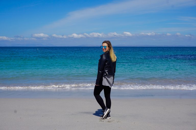 Woman standing on the beach of Inis of the Aran Islands tour.