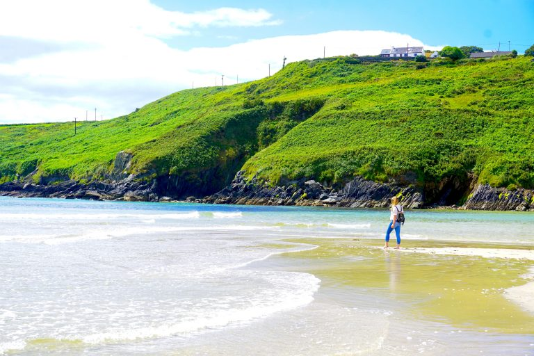 Woman on an Ireland working holiday visa standing on sandy beach with lush, green landscape. Barleycove Beach is located in West Cork.
