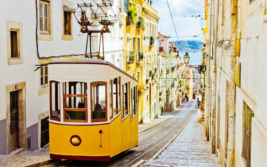 The tram 28 in Lisbon Portugal is a yellow car that travels through the small old town of Lisbon. It is still used by locals and is also a popular Lisbon experience.