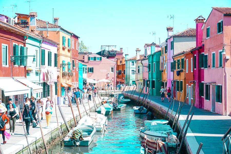 Canal with fishing boats surrounded by pastel-colored houses in Burano Island, Italy. The island is just a boat ride from Venice, perfect for a Northern Italy travel Itinerary.