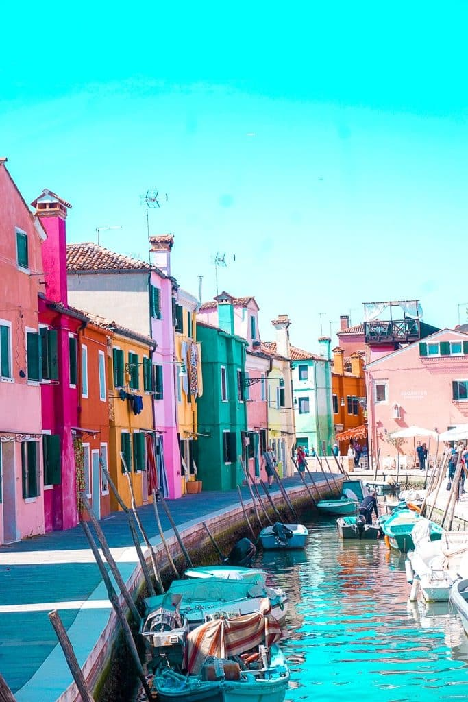 A line of colorful, pastel houses in Burano, Italy overlooking the canals. Burano is a day trip from Venice.