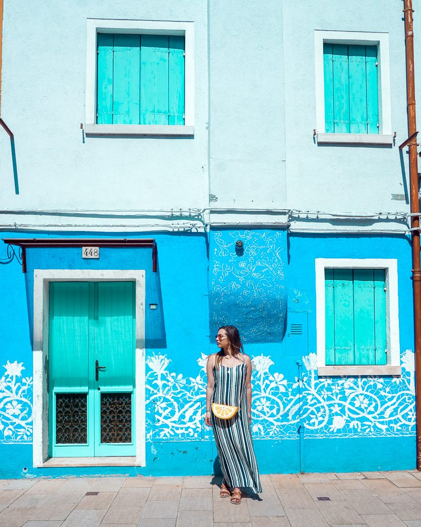 Woman standing next to a blue, floral panted house in Burano, Italy.