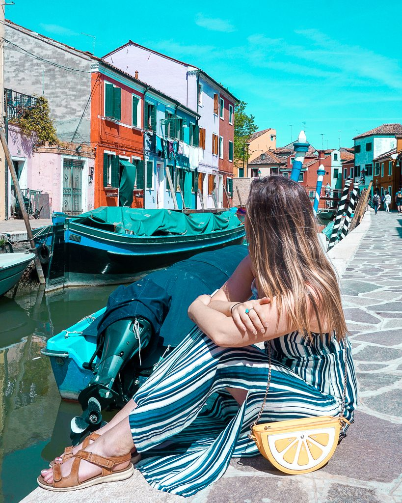 Woman in striped dress sitting near the canals of Burano Italy, a perfect addition to a Northern Italy travel Itinerary