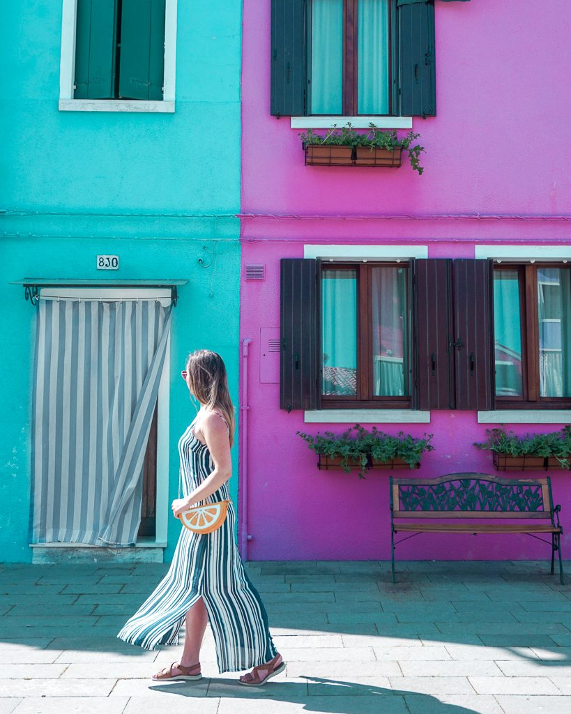 Woman walking in striped dress next to a blue and purple house in Burano Italy.