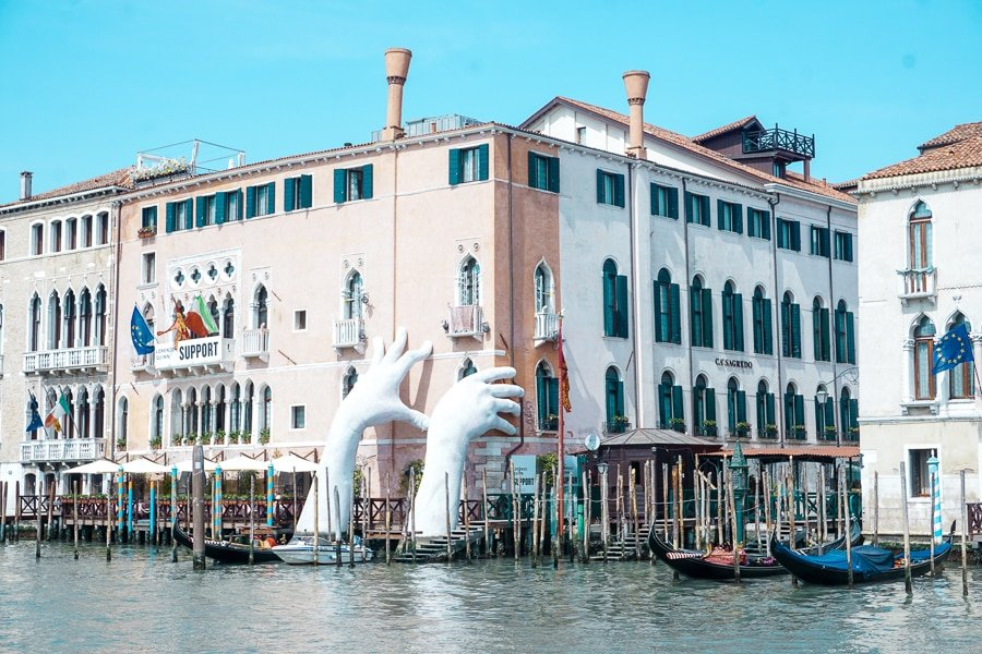 """Support"" by  Lorenzo Quinn in the canals in Venice Italy features two giant hands coming out of the water climbing a building. The structure is highlighting climate change in Venice."