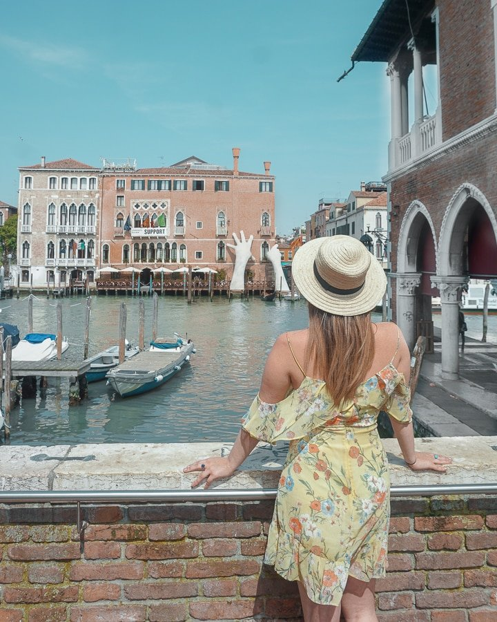 woman in yellow dress and sun hat overlooking venice canal in Italy.
