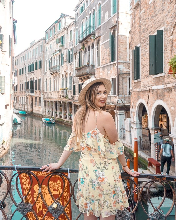 Woman standing while looking over the Venice canals in Italy, a perfect addition to a Northern Italy itinerary.