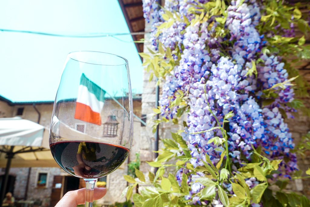 Wine glass with wisteria flowers and Italian flag in the Verona region. Verona is an ideal base for a Northern Italy travel Itinerary.