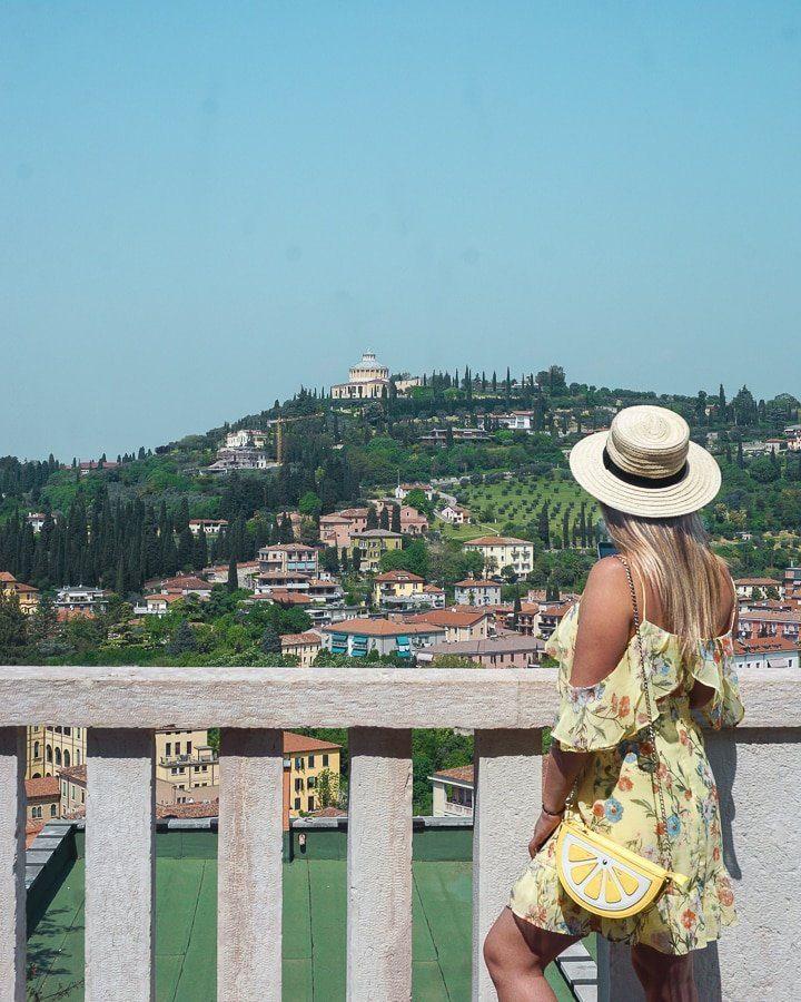 Woman with hat and yellow dress overlooking a valley in Verona, near  Verona's Castel.