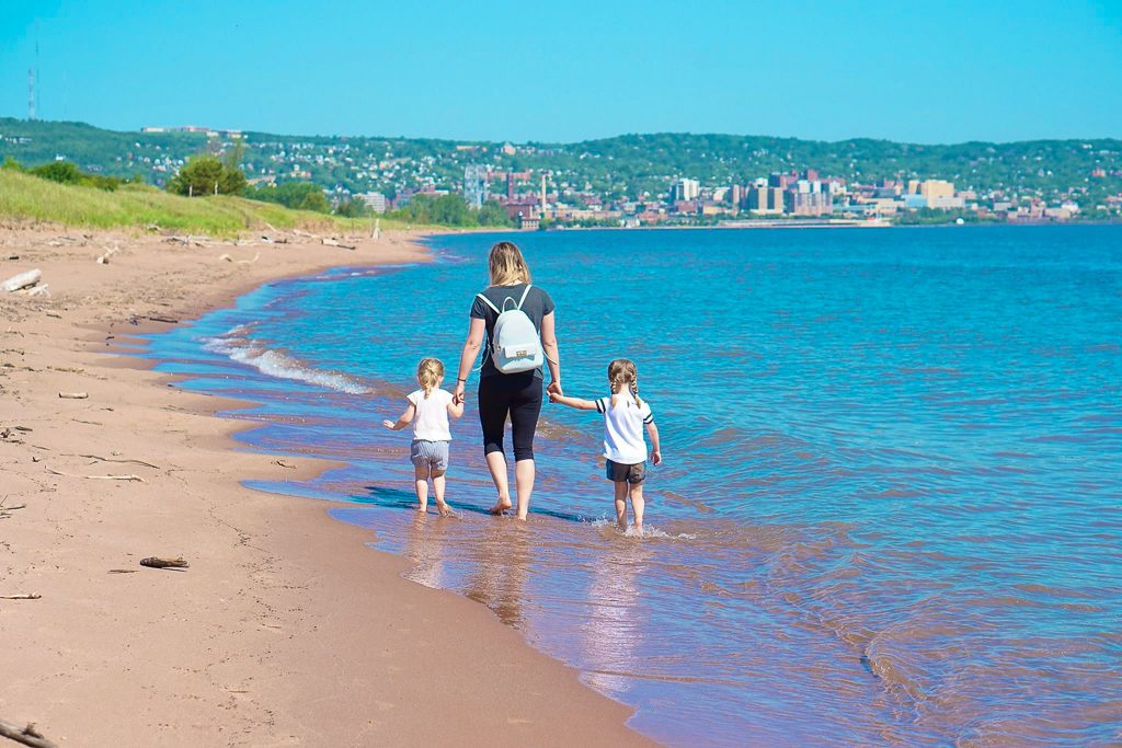 A woman walking with two children along park point beach in Duluth, Minnesota in summer.