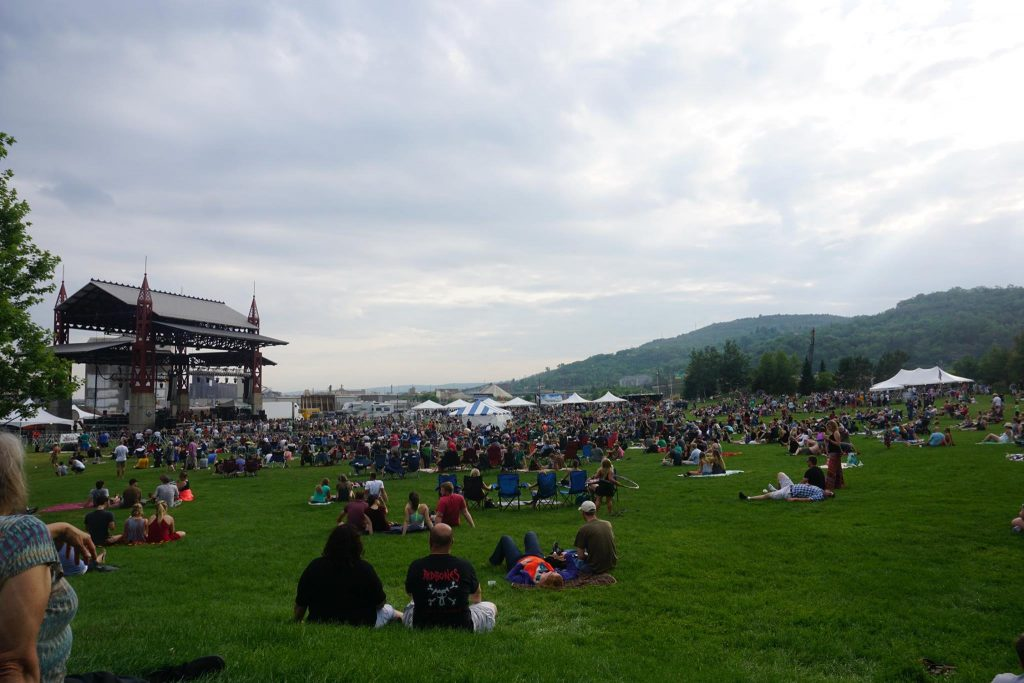 A crowd of people sitting near a stage at bayfront music festival in Duluth, Minnesota