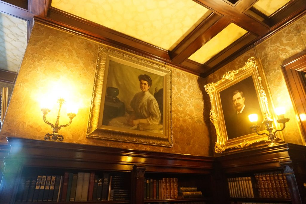 A tour inside the Glensheen mansion estate, featuring framed photos of family members with candles and victorian-era wall paper.