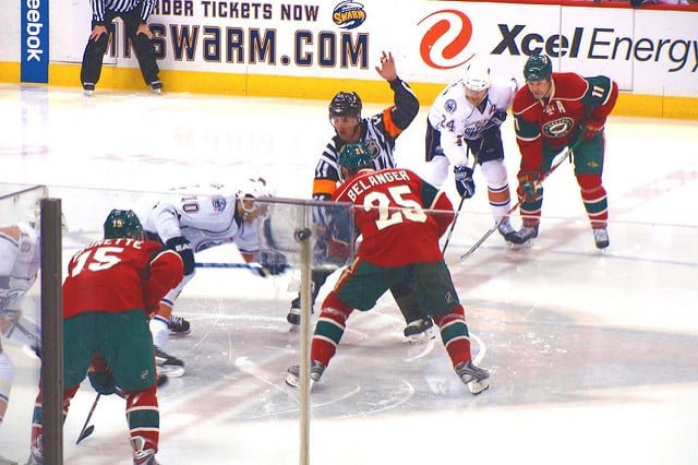 The St. Paul Minnesota wild hockey team playing at the xcel energy center. The photo features a close up shot with the wild vs. Edmonton Oilers during a face off.