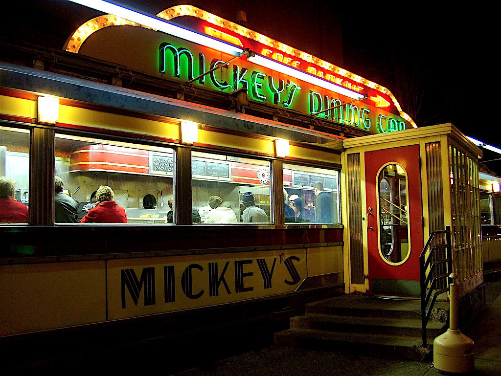 The iconic Mickey's diner in St. Paul Minnesota, which is a small 1950s-style dining car. The outside is illuminated with lights, open 24 hours a day.