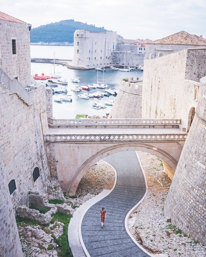 aerial view of woman walking along pathway under a stone pathway of Dubrovnik's old town.