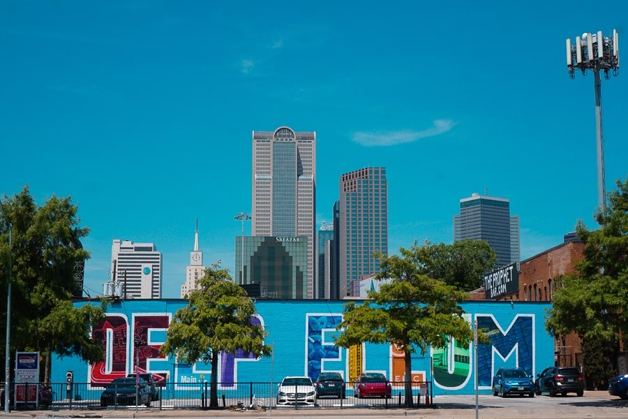 Multi-colored Deep Ellum mural in front of the Dallas skyline on a summer day. Mural located in The Doors Club Parking Lot.