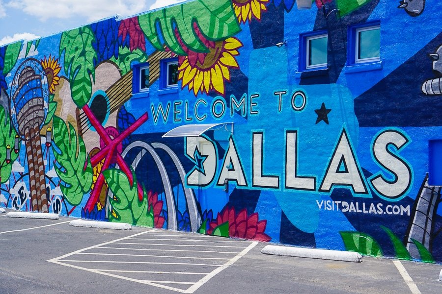 Welcome to Dallas mural with blue, floral design in Health Arts Consulting parking lot in Deep Ellum.