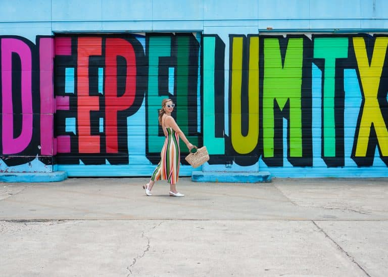 Woman walking in front of Deep Ellum rainbow mural at 208 Malcom X Blvd.