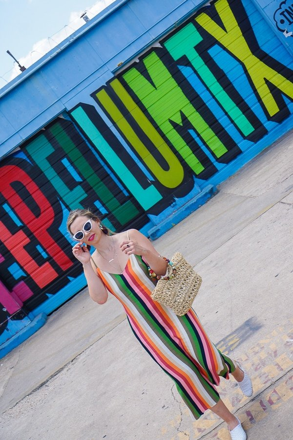 "Woman wearing a rainbow striped dress walking in Deep Ellum Texas. Behind is a rainbow mural that says ""deep ellum tx""."