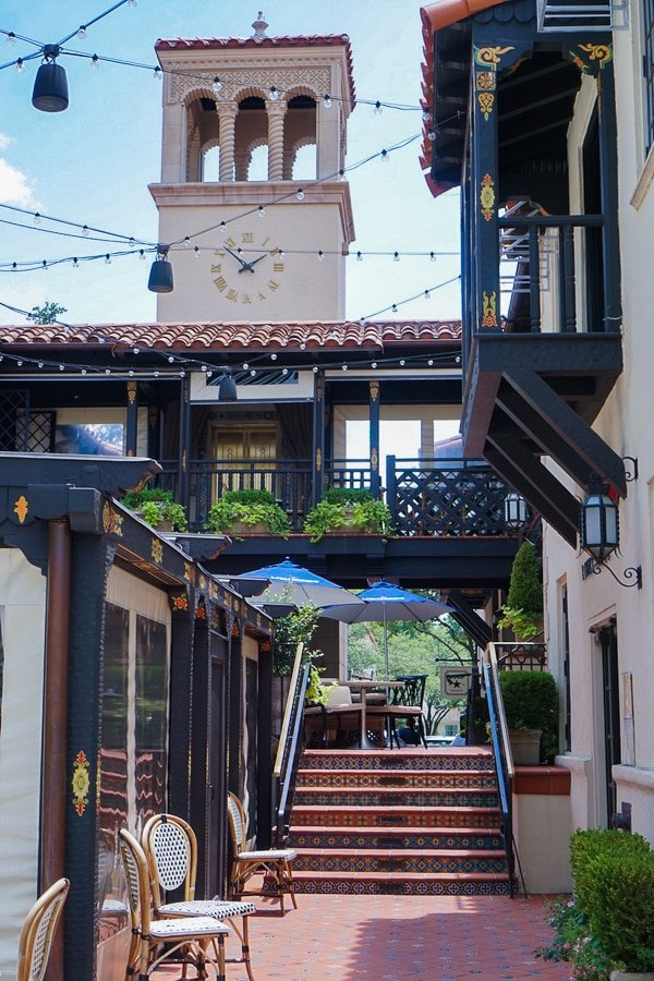 City square in Highland Park Village with a clock tower and Spanish-style decor and tiles.