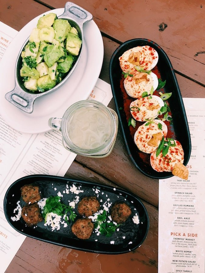 A flat-lay of deviled eggs, meatballs, avocado salad, and a mojito on a picnic table. Photo taken at The Rustic, in Dallas, Texas