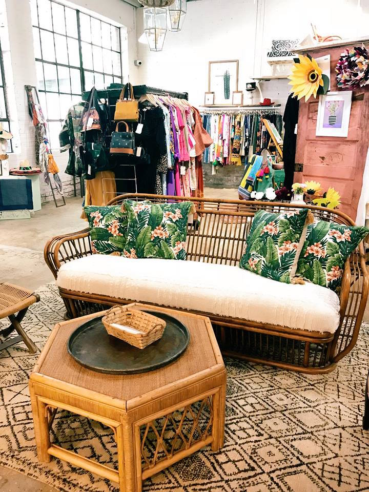 A woven couch and ottoman and vintage clothing racks with boho decor. Photo taken at Flea Style in Deep Ellum