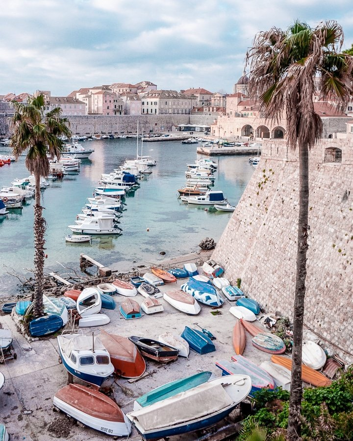 View from Ploce Gate walking into Dubrovnik's Old Town of Palm Trees, Colorful boats, and the Old Harbor surrounded by the Stone City Walls.
