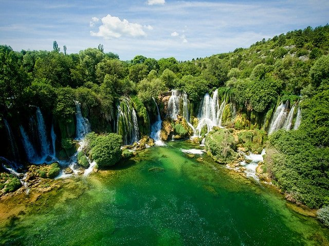 Kravice Waterfalls near Mostar, featuring a lush green forest and 20 separate waterfalls. Kravice is a popular Dubrovnik day trip during the summer.