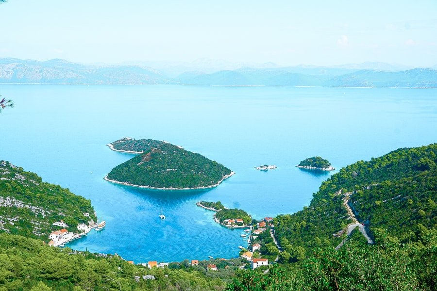 Panoramic view of the Adriatic Sea and green landscape from the island of Mljet. Photo features the Prozura Bay, with an island shaped like a heart.
