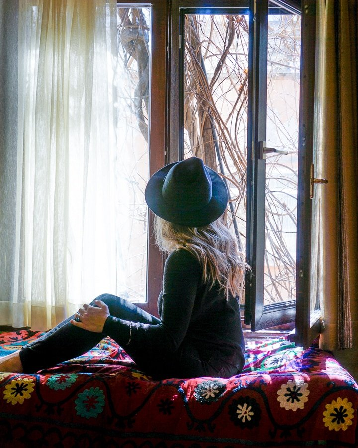 Woman sitting by a window in Istanbul inside Hotel Empress Zoe, in the Old Town of Istanbul