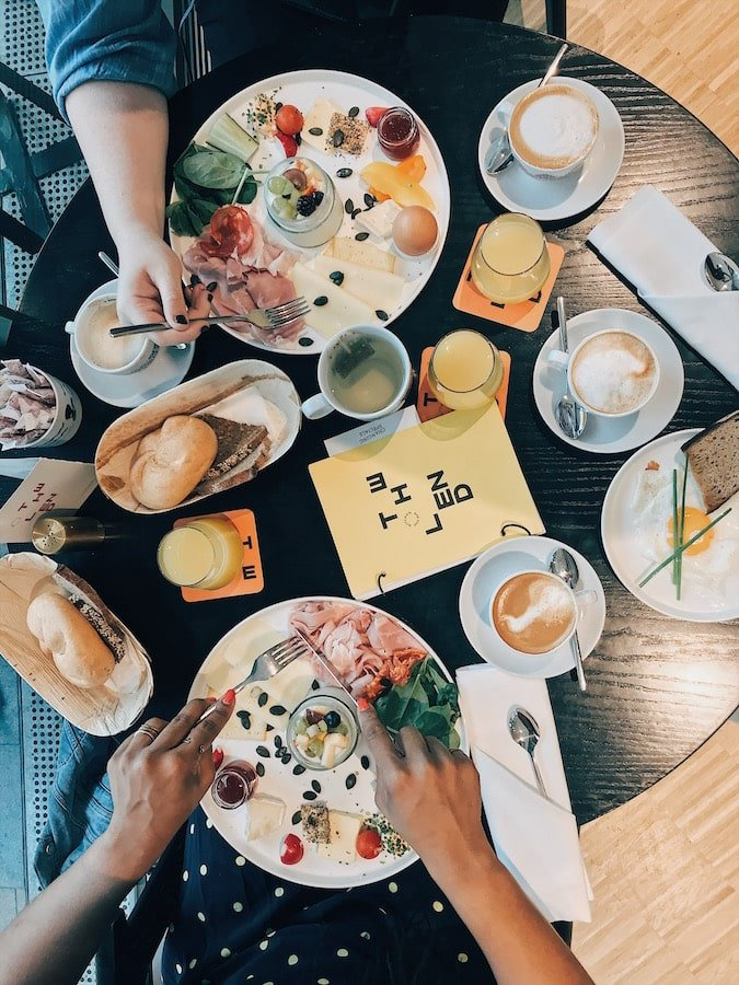 Local brunch at the Lend Hotel in the culinary capital of Austria: Graz. Flat lay of cheese, ham, bread, eggs, coffee, and jams with two women eating.