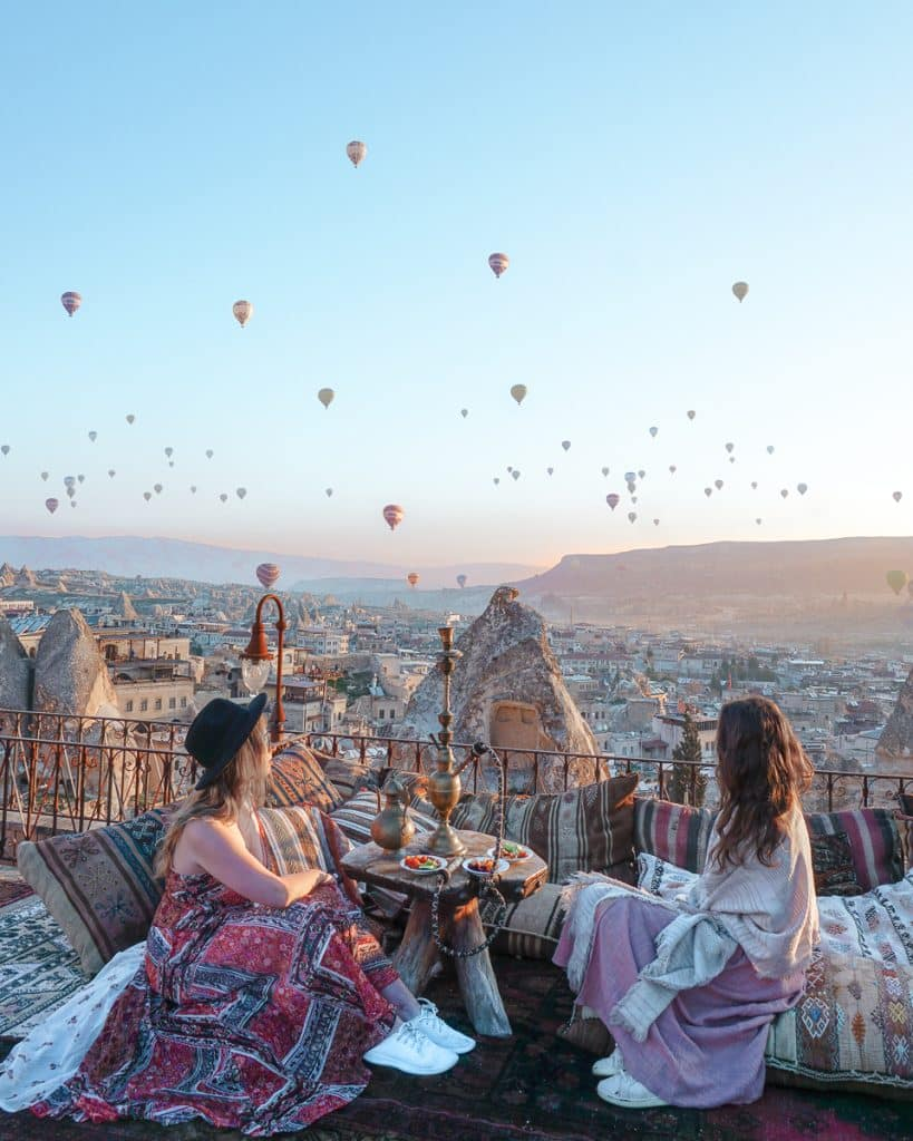 Two women at a cave hotel in Goreme overlooking the sunrise surrounding by hot air balloons and rock formations.