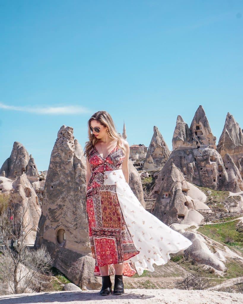 Women standing in front of the Greek village of Cavusin in Cappadocia, Turkey.