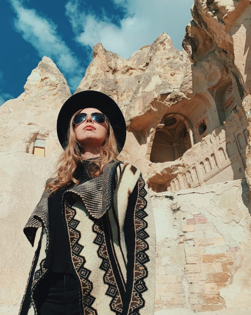 woman standing in front of the rock-cut houses in the open air museum in Cappadocia, Turkey. This one of the most popular cappadocia tours to take