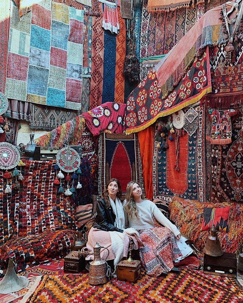 Goreme Carpet store in Cappadocia, Turkey filled with colorful rugs and two women sitting.