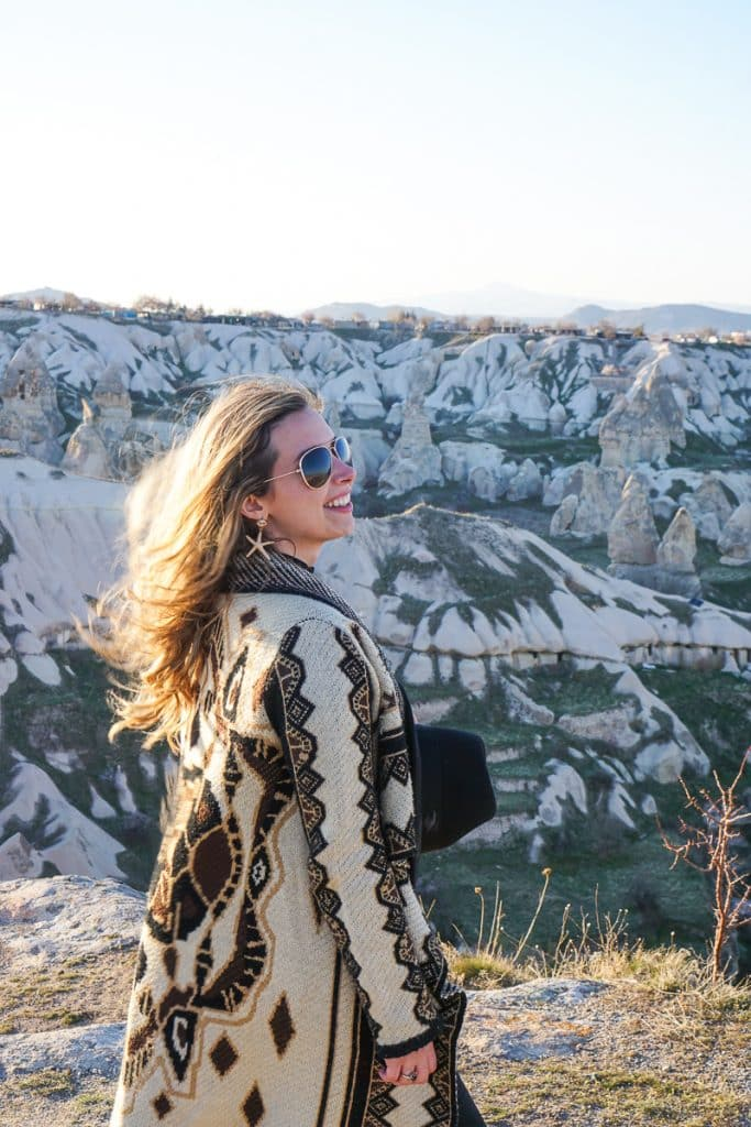 Women with wind blowing in her hair overlooking the Cappadocia cliffs in Goreme.