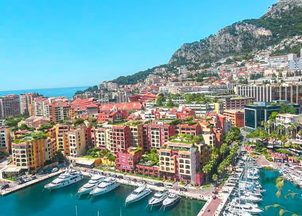 Nice to Monaco: day trip from Nice. Colorful buildings overlooking a harbor on the sea.