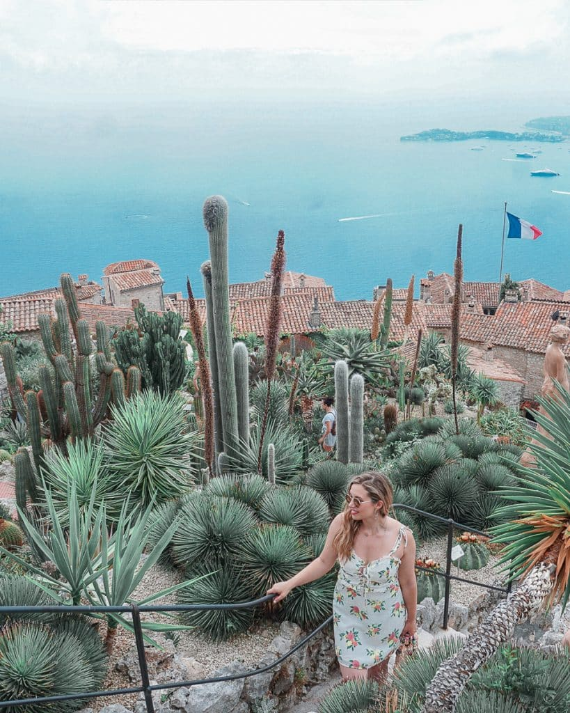 Woman overlooking the succulents and sea from the hilltop Eze village, one of many popular day trips from Nice, France.