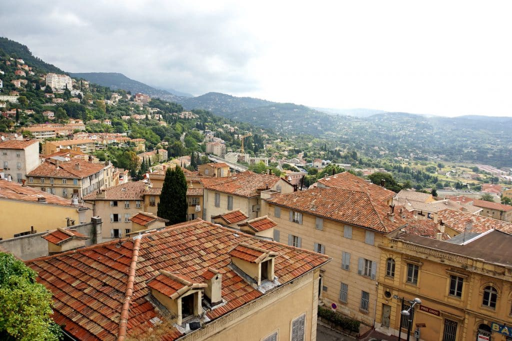 Grasse, one of the popular day trips fron Nice. Town is covered in orange houses surrounding by green hills and mountains.