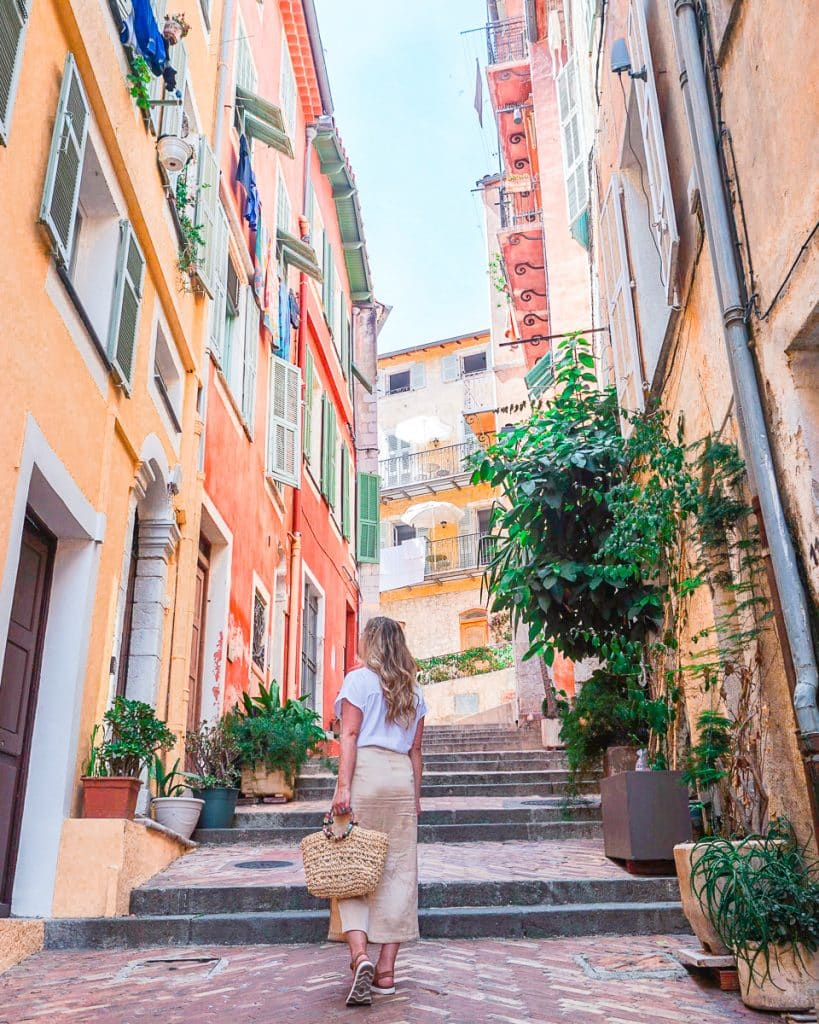 Woman walking up colorful street in Villefranche sur mere.