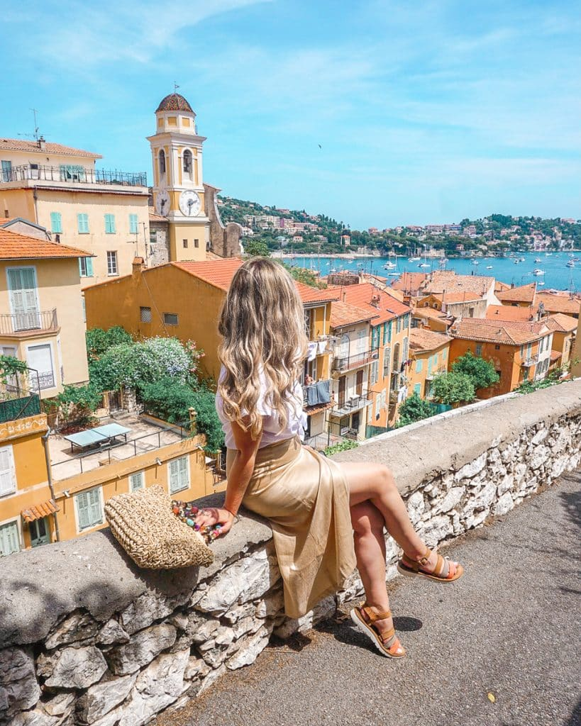 Woman sitting on stone ledge overlooking colorful town of Villefrance Sur Mer, a popular day trips from Nice.