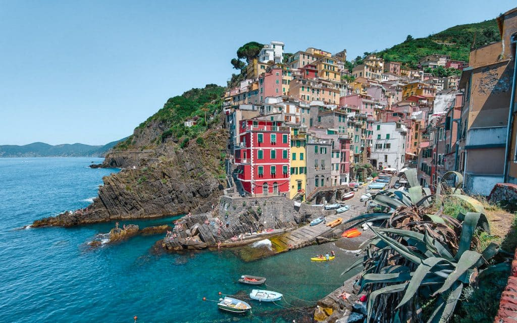 Riomaggiore: Cinque terre train travel guide. Coastal fishing village with colorful houses on a cliff.